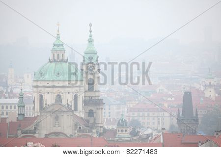 Saint Nicholas Church in Mala Strana viewed in the mist from Petrin Hill in Prague, Czech Republic.