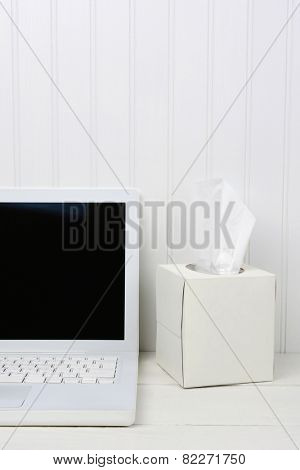 Closeup of a white wood desk with a white laptop and a white box of facial tissues. Vertical format with a beadboard background.