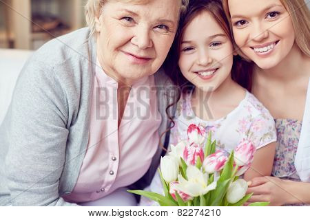 Happy little girl, her mother and grandmother with fresh tulips