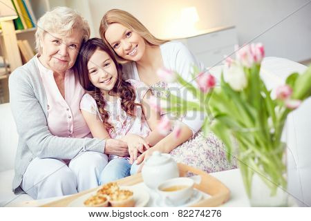 Little girl, her mother and grandmother sitting on sofa together