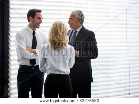 three businesspeople standing up and speaking