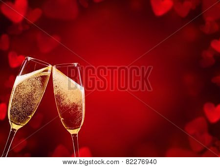 Two glasses of champagne with abstract blur background made of hearts shapes