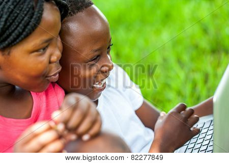 African Kids Having Fun On Laptop Outdoors.
