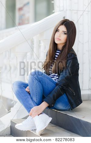 Portrait of a beautiful young woman sitting on the steps.