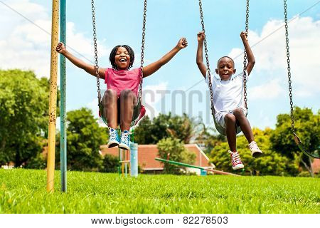 African Kids Playing On Swing In Neighborhood.