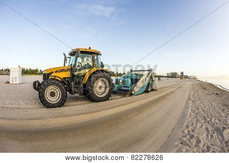 Man Prepares The Beach Early Morning With The Tractor