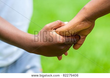 Detail Of African Boy Holding Girls Hand.