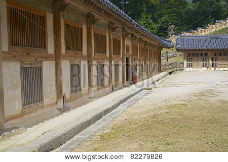 Buddhist monk stands at the entrance to the Tripitaka Koreana storage building.