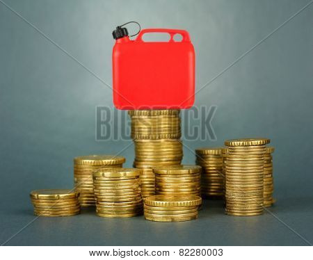 Fuel canister on stack of coins on gray background