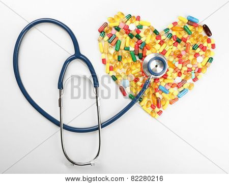 Stethoscope with heart from pills isolated on white