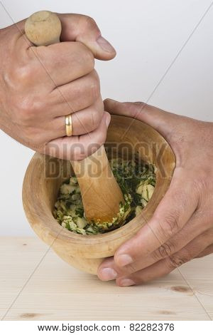 Chef Crushing Garlic And Parsley With Mortar And Pestle In The Kitchen