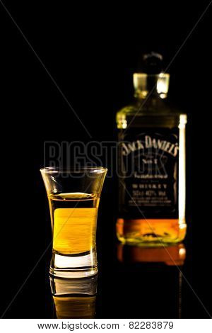 Whisky in a shot glass, bottle of Jack Daniel's blurry in the background