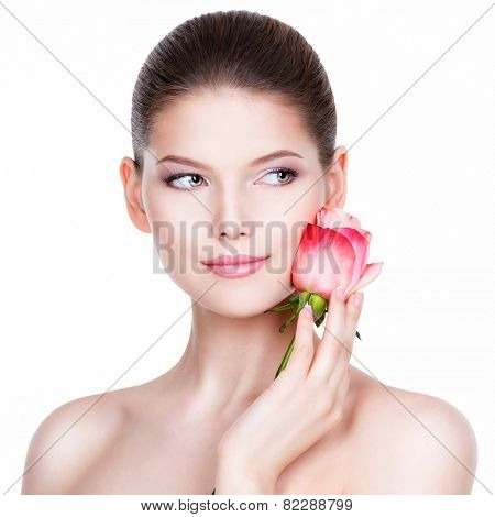 Beautiful young woman with pink rose. Beauty treatment concept. Portrait over white background.