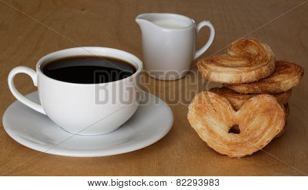 Coffee cup, the milk jug and cookies