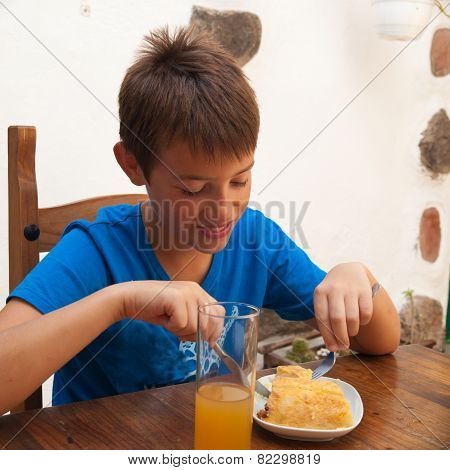Tanned Caucasian Boy Eating A Portion Of Tortilla In A Cafe