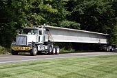 stock photo of oversize load  - Delivering concrete supports for the bridge over the freeway under construction - JPG