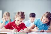 picture of diligent  - Portrait of two diligent classmates at lesson - JPG