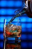 stock photo of whiskey  - whiskey with ice on a glass table - JPG