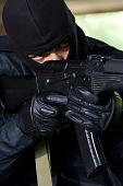 foto of extremist  - Trooper in black mask targeting with a gun - JPG