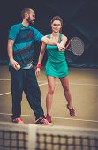 image of  practices  - Woman player and her coach practicing on a tennis court - JPG