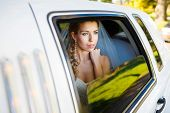 foto of limousine  - Bride looks out of the window a white limousine - JPG