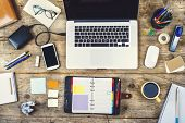 picture of hard-on  - Mix of office supplies and gadgets on a wooden desk background - JPG