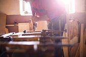 image of carpenter  - Hands of carpenter screwing a glue clamp to join wooden planks together - JPG