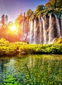 picture of waterfalls  - Majestic view on waterfall with turquoise water and sunny beams in Plitvice Lakes National Park - JPG