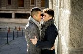 foto of homosexuality  - young happy attractive gay men couple holding hugging and kissing each other outdoors on street in free homosexual love concept in urban background - JPG