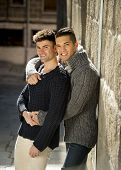 picture of homosexuality  - young happy attractive gay men couple hugging and posing outdoors on street in sexual freedom and free homosexual love concept in urban background - JPG