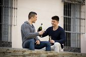 image of gay couple  - young attractive hispanic gay men couple celebrating together Valentines day or anniversary champagne toast on street smiling happy in love on urban background - JPG