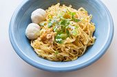 image of noodles  - delicious yellow noodle with fish ball in blue bowl on the white cutting board - JPG