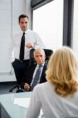 image of 55-60 years old  - Three businesspeople having a meeting in the office - JPG