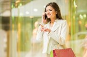 pic of people talking phone  - Beauty woman with shopping bags in shopping mall is talking by phone - JPG