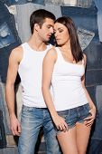 stock photo of denim jeans  - Beautiful young couple in tank tops and jeans standing close to each other and against jeans background - JPG