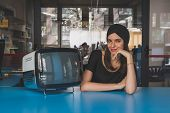 foto of turban  - Beautiful young brunette with turban posing beside a vintage tv - JPG