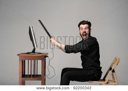 Angry man is destroying a keyboard