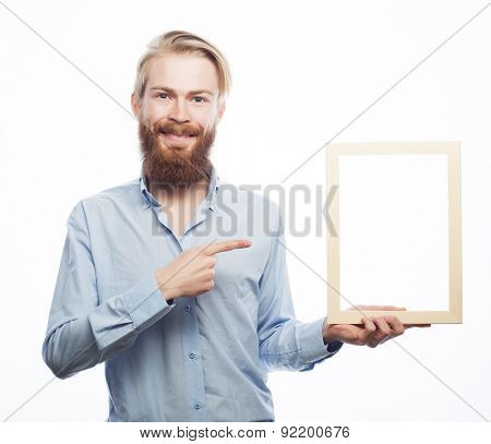 Copy space in picture frame. Handsome young bearded man in blue shirt holding a picture frame and pointing it with smile while standing isolated on white background