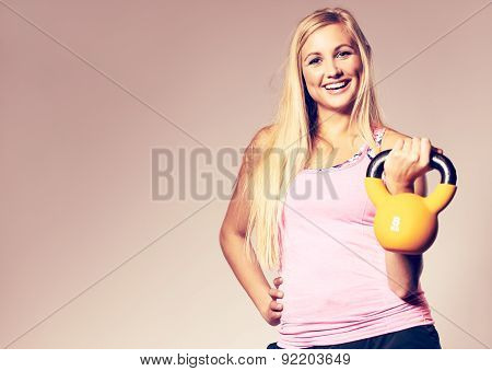 Woman Wearing Workout Clothes Holding A Kettlebell.