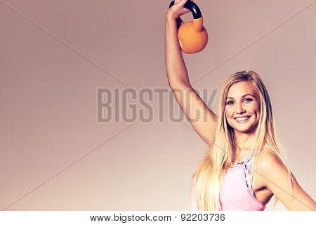 Woman Smiling At Camera And Lifting Kettlebell.