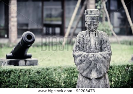 Stone statue of old chinese sage in traditional clothing