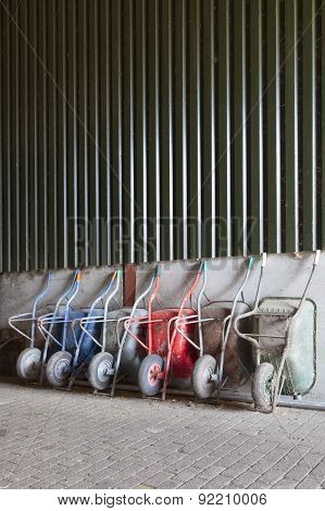 Six Wheelbarrows Rest Against Wall Of Farm Barn