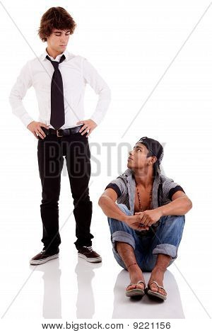 Two Men Of Different Ethnicity, One Sitting Looking At The Other Standing, Isolated On White, Studio