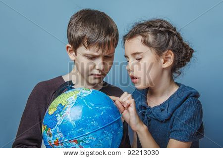 Teenage boy with a girl looking at a globe girl opened her mouth