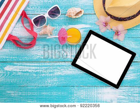 Blank empty tablet computer, summer accessories on beach.