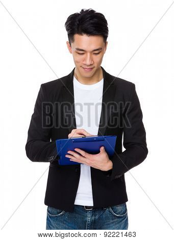Asian young man write on clipboard
