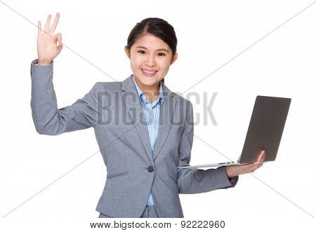 Asian businesswoman use of laptop and ok sign gesture