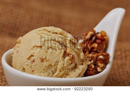 A fresh homemade scoop of walnut ice cream with nuts in a bowl
