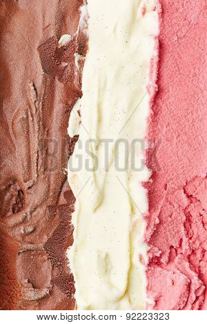 Stripes of neapolitan ice cream from above with chocolate, vanilla and strawberry ice cream