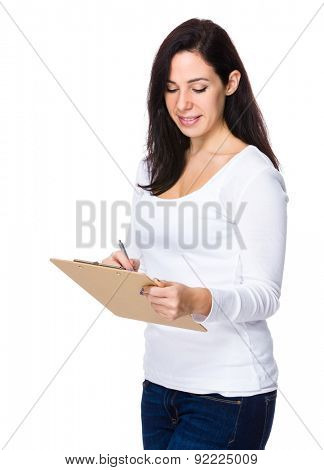 Brunette woman write on clipboard